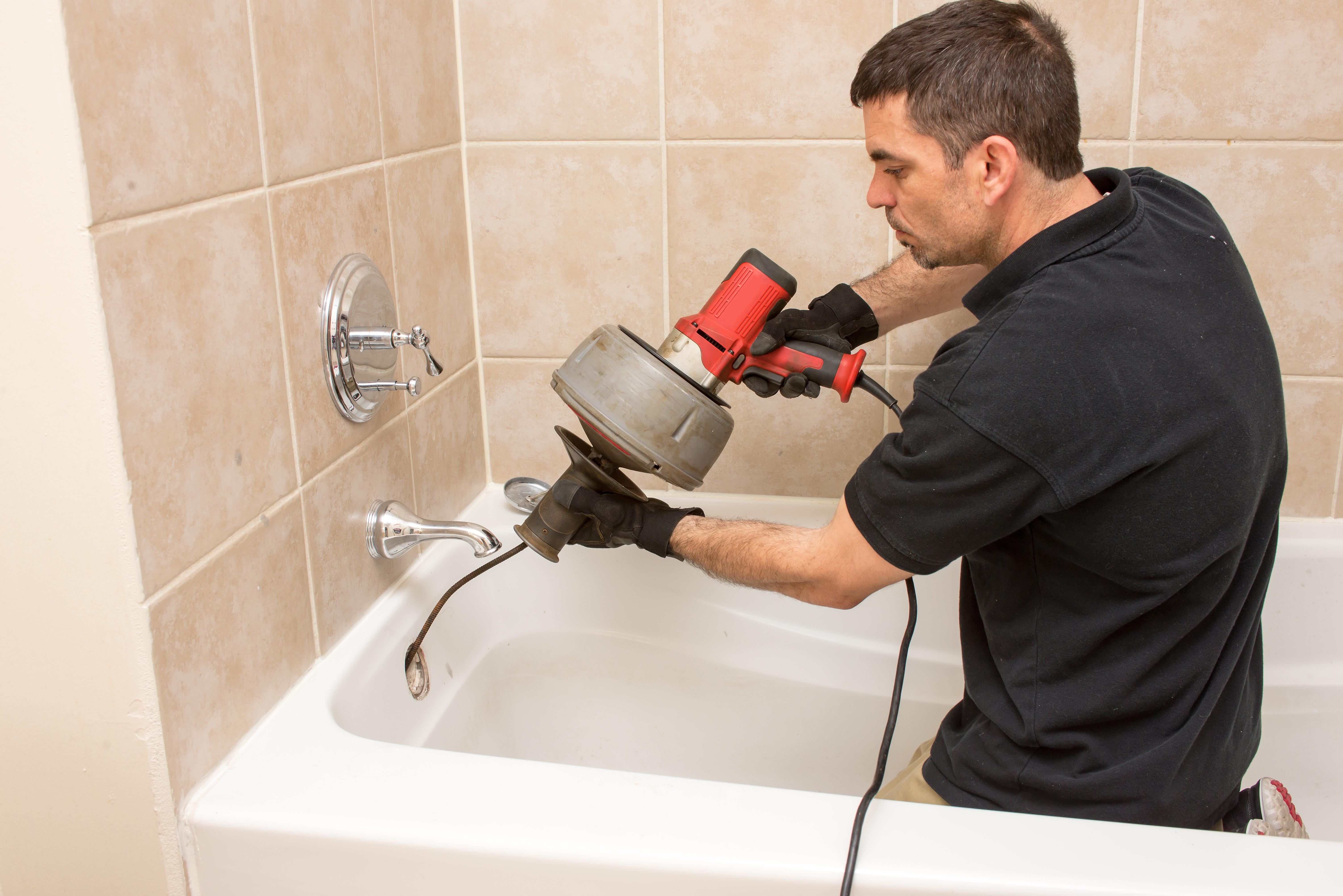 A plumber runs a drain snake down a clogged tub drain.
